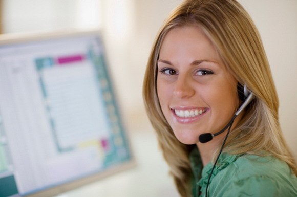 Smiling woman with headset and computer monitor